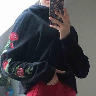Svart hoodie med rosor broderat på ena ärmen och luvan, kortare modell. Superfint skick, knappt använd. Köparen betalar frakten💕