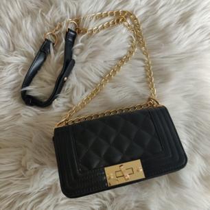 Väska från Nelly i fakeskin med guldkedja, liten modell.