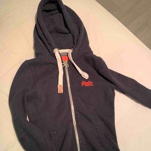 Marinblå hoodie från Superdry i storlek XS. Köparen står för frakt så vidare man inte har möjlighet att mötas upp i närheten av Helsingborg.