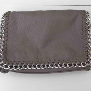 En sidoväska från tiamo. Säljer därför att den inte kommer till användning för har andra väskor.  Dragkedjan är silver och själva väskan är beige/grå. Frakt 72. Köpt för 499kr.