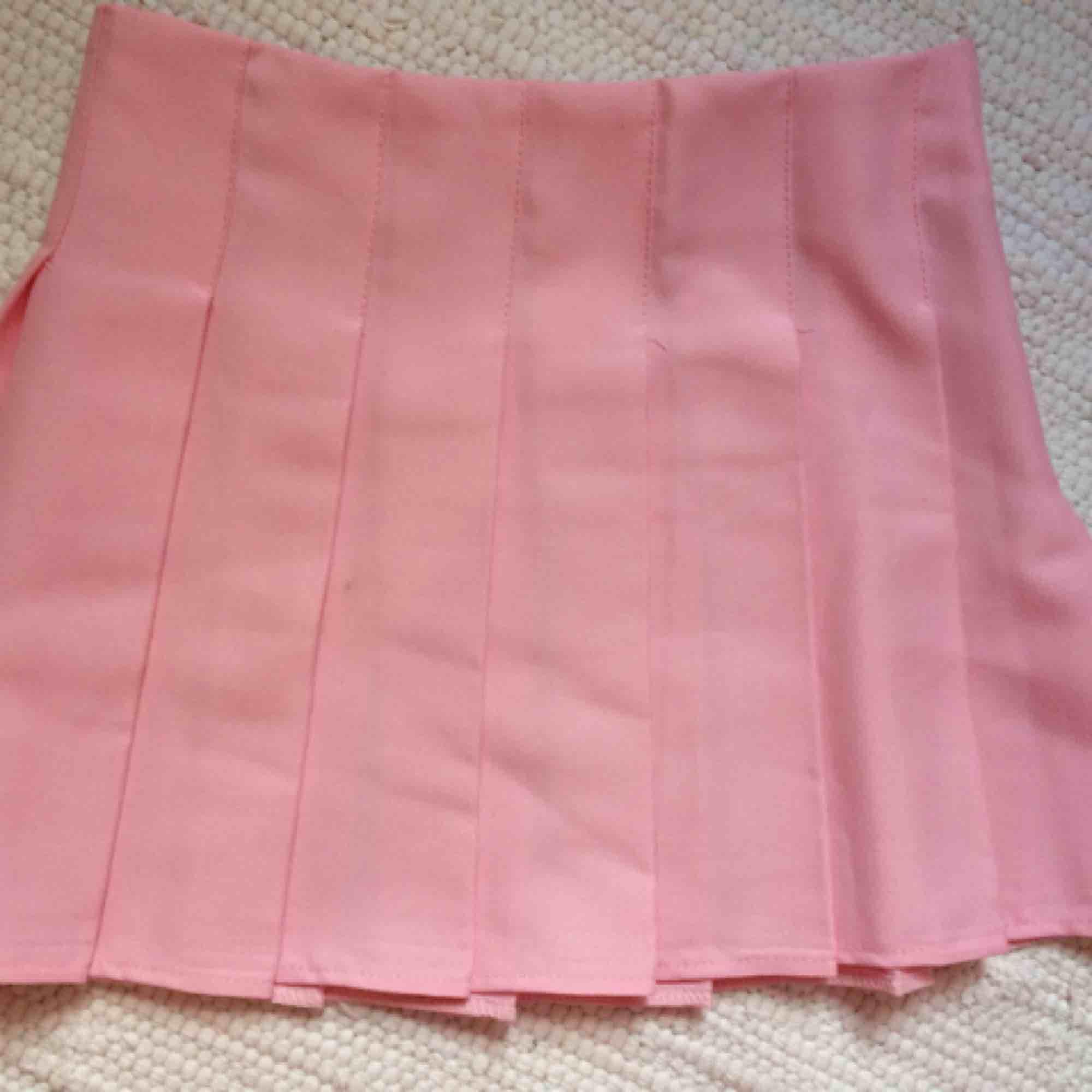 Rosa veckad kjol, aldrig använd eftersom den var för stor. Storlek S. Kjolar.