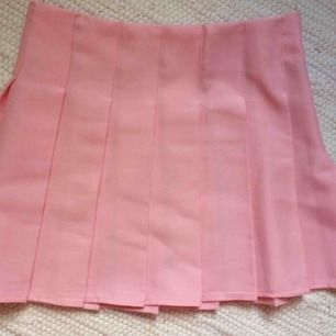Rosa veckad kjol, aldrig använd eftersom den var för stor. Storlek S