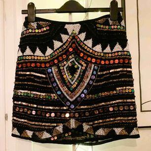 Paljett broderad kjol från River Island. Jättefint plagg som jag tyvärr inte använt, då den är köpt i för liten storlek. Mått: midja 72 cm, Längd mitt bak 43 cm.