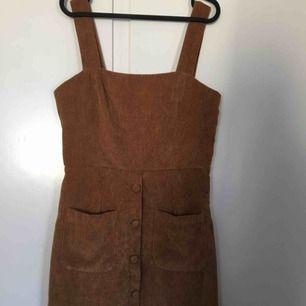 En brun/randig klänning i storlek 38 men funkar även som 40  (Köpare står även för frakt) eller mötes i Linköping