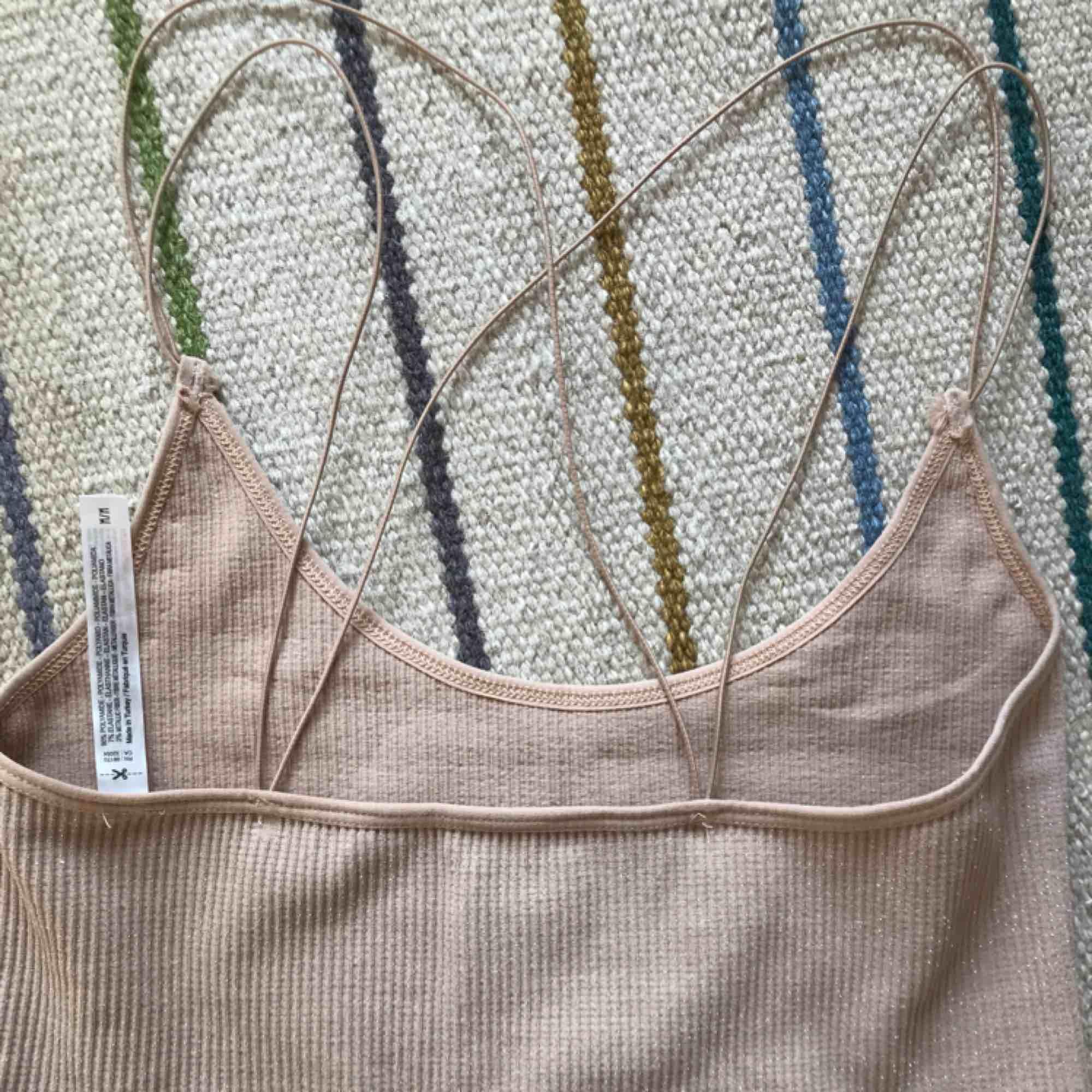 Glittrigt rosa/beige linne som korsar i ryggen, från Urban Outfitters. Stl M men passar även S!. Toppar.
