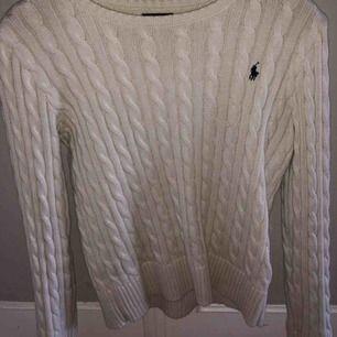 Välanvänd kabelstickad Ralph Lauren tröja i fint skick. Köptes i USA därav storleken men sitter som en xs. Köptes för ca 1000 kr. Köparen står för frakt.