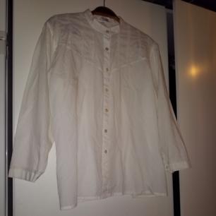 Vit halvtransparent skjorta med fina detaljer. Märkt med storlek 44 men passar mindre