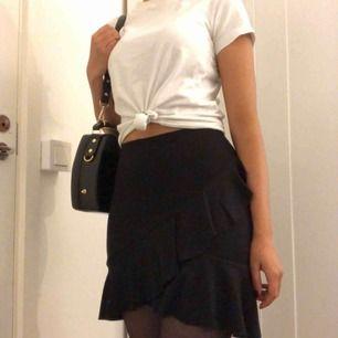 En tajt volang kjol som är lite längre bak. Är i trikåt material och garanterar en snygg rumpa! (: Endast använd 1 gång.