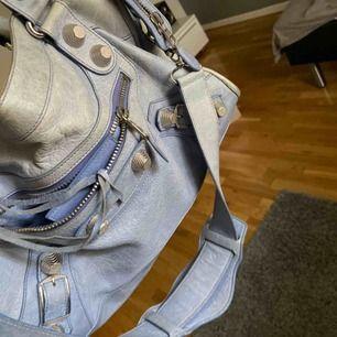 Väskan är en fin blå/ljusblå. Den är väl använd och lite solblekt på vissa ställen men den är fortfarande väldigt väldigt fin. Längd: 38 cm/Höjd: 25 cm  Spegel finns med. Väskan är självklart äkta men saknar äkthetsbevis (därav det låga priset)
