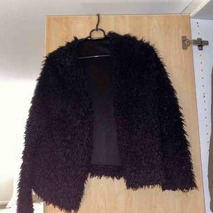 En svart pälsjacka i storlek S. Ej äkta päls