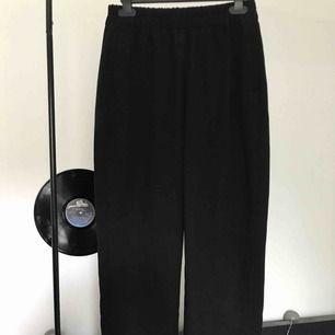 Svarta kostymbyxor med fickor på båda sidorna och igensydda fickor bak