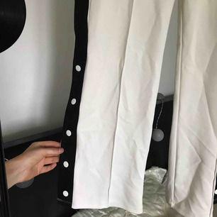 Svartvita knappbyxor i samet med fickor på båda sidorna från Junkyard