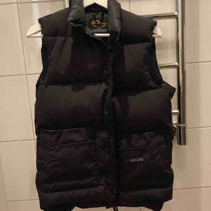 En canada goose dunväst i svart.  Storlek XS men då kläderna från canada goose är rätt stora i storleken så skulle jag säga att denna passar bäst på en 36/38.  Användt endast några gånger å är i mycket fint skick.  Vid snabb affär, billigare pris