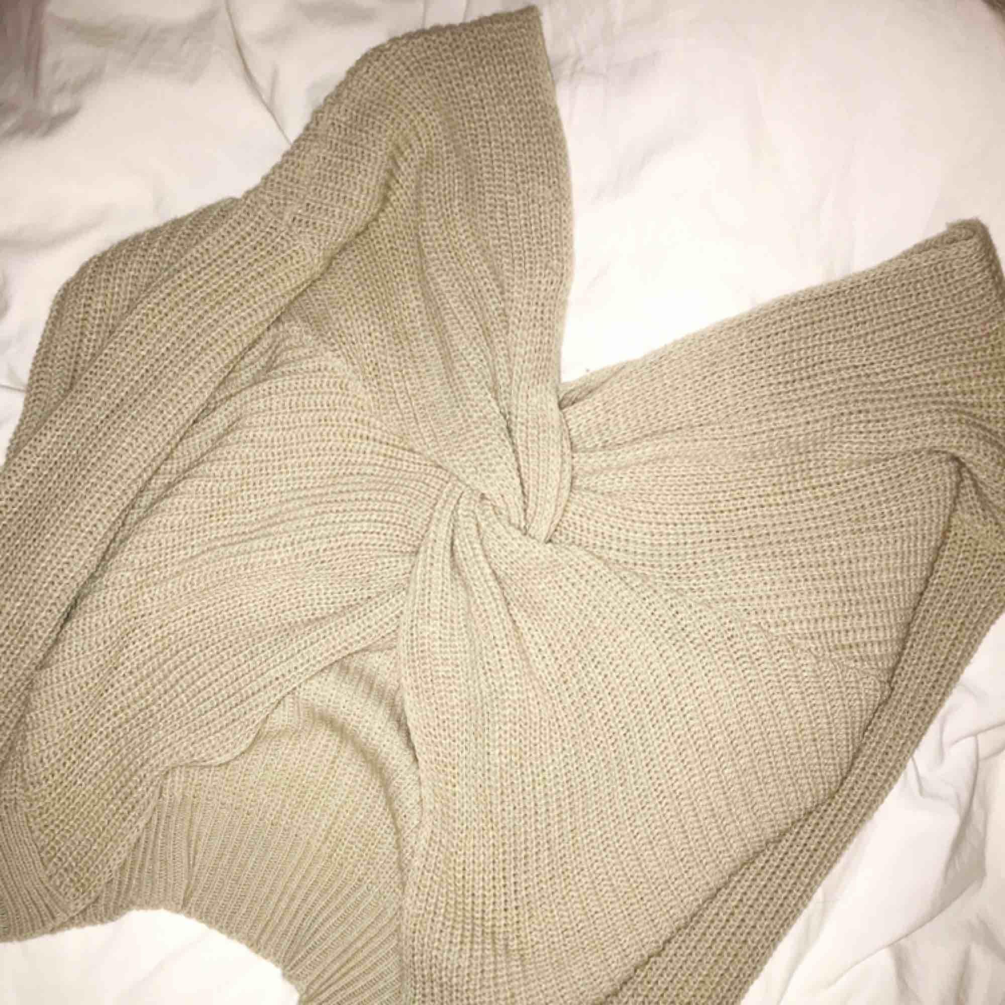 Beige stickad tröja med knytning som man kan ha både bak och fram. Passar nog de flesta storlekar. Kommer tyvärr aldrig till användning. Frakt kostar 40kr 🥰. Stickat.