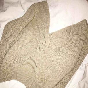 Beige stickad tröja med knytning som man kan ha både bak och fram. Passar nog de flesta storlekar. Kommer tyvärr aldrig till användning. Frakt kostar 40kr 🥰