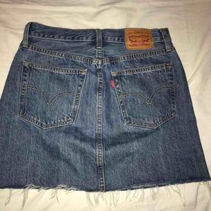 En mörkblå jeanskjol med slitningar vid kanten från Levi's. Använd ca 3 gånger och är i bra skick som ny. Nypris: 599kr säljer för 350kr (pris kan diskuteras)