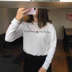 Mysig vit Tommy Hilfiger tröja som går att spänna i midjan. Den är i storlek XS men skulle säg att den passar S också. Använd bara ett par gånger. Köpt på Pacsun