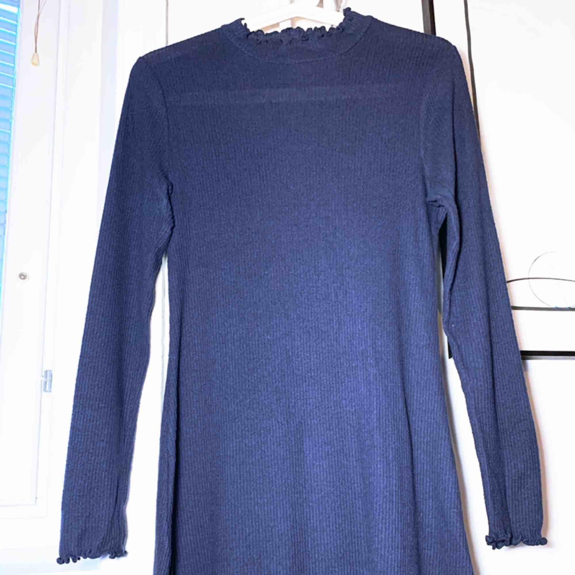 Stickad polo-klänning från Pins and Needles, perfekt att ha under koftor till hösten. Materialet är mjukt och nopprar inte, 76% Rayon, 20% polyester och 4% elestane. Modellen är lätt utsvängd och följer midjan. Längd mitt bak: 80cm.. Klänningar.