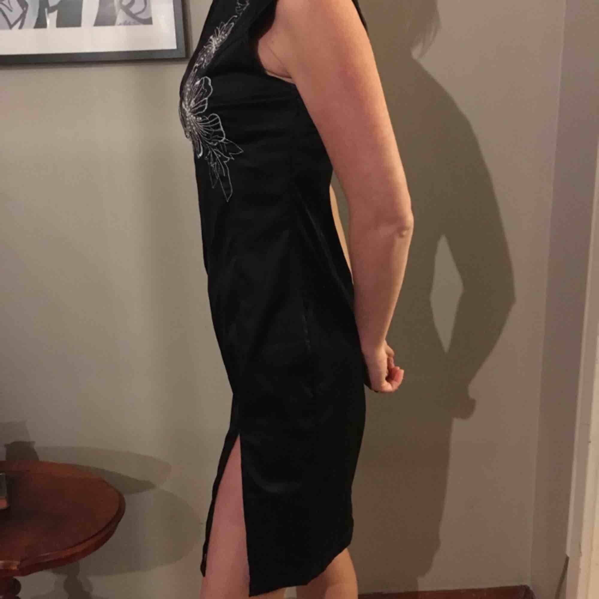 Svart tight klänning i svart sidenlook med superfina blomdetaljer av paljetter. Slits på ena benet och en lite högre krage med en läcker urringning. Klänningar.