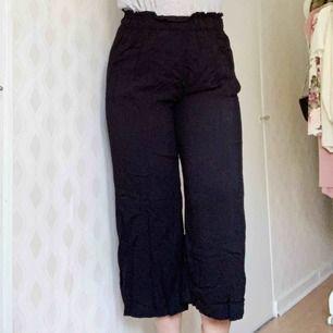 Svarta sköna byxor i lösare passform. Benen är breda och något kortare än vanliga byxor.