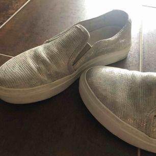 Silvriga slipons skor.  Vet tyvärr ej vart dom är ifrån och är lite osäker vad det är för storlek, dessa är ungefär som storlek 37 i vans slipons. Köpta för ca 1000kr  Betalning sker via swish