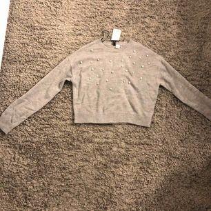 en grå stickad tröja med lite pärlor, helt oanvänd