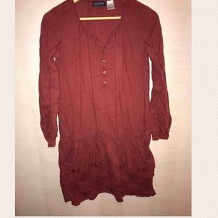 Roströd knälång klänning med spets och fickor