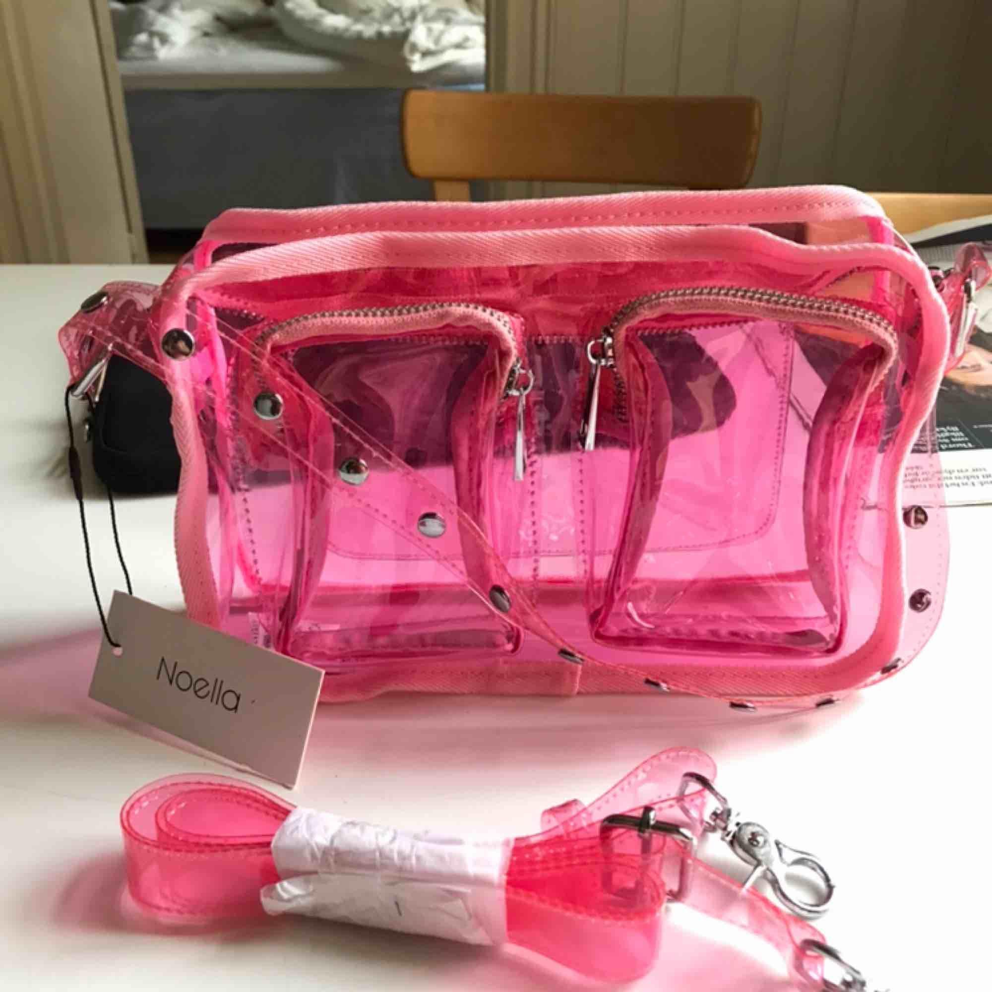 Hej! Säljer denna väska från noella med pristag kvar i en cool rosa neonfärg. Hör gärna av dig vid frågor ☺️ Både långt och kort strap följer med.   Köptes för: 799kr. Väskor.