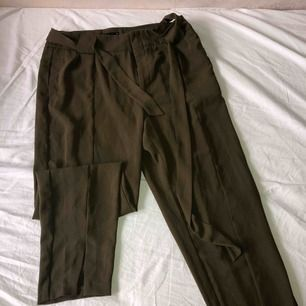 Khaki färgade kostym byxor från Gina tricot, med split längst ner på byxorna.