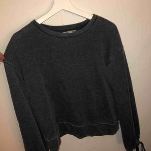 En tröja med snörning längst ner på armarna. Kunden ansvarar för frakten