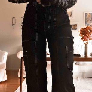 Svarta byxor med vita kontrastsömmar från Weekday i storlek 36. Supersköna och stretchiga. Använda 2 gånger, och köpta för ca 1 månad sedan med ett nypris på 500 kr. Jag är 167 cm och på mig är dem perfekta i längden och med hög midja