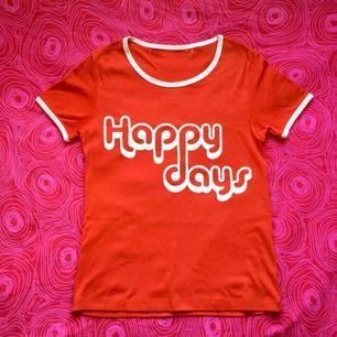🍎 Röd t-shirt med vitt tryck där det står 'Happy days'. Obs! Det finns sprickor i texten 🍎