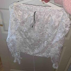 Jättefin vit tröja med spetstyg överst, med armar men den är öppen vid axlarna. Aldrig använd