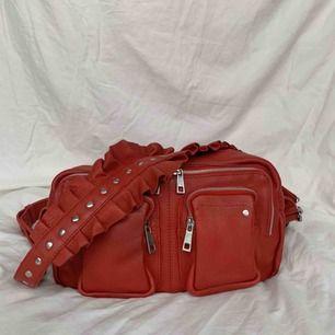 Röd väska från Nùnoo i modellen Alimakka. Det är en limited edition väska med ett avtagbart band med volang. Det andra bandet är justerbart. Äkta kalvskinn. Väskan är i nyskick, använd mycket sparsamt. Nypris: ca 1600kr.