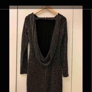 Superfin klänning med öppen rygg i glittrigt tyg. Storlek small. Endast använd en gång och är i fint skick. Passar perfekt till tex nyår eller andra festliga tillfällen.