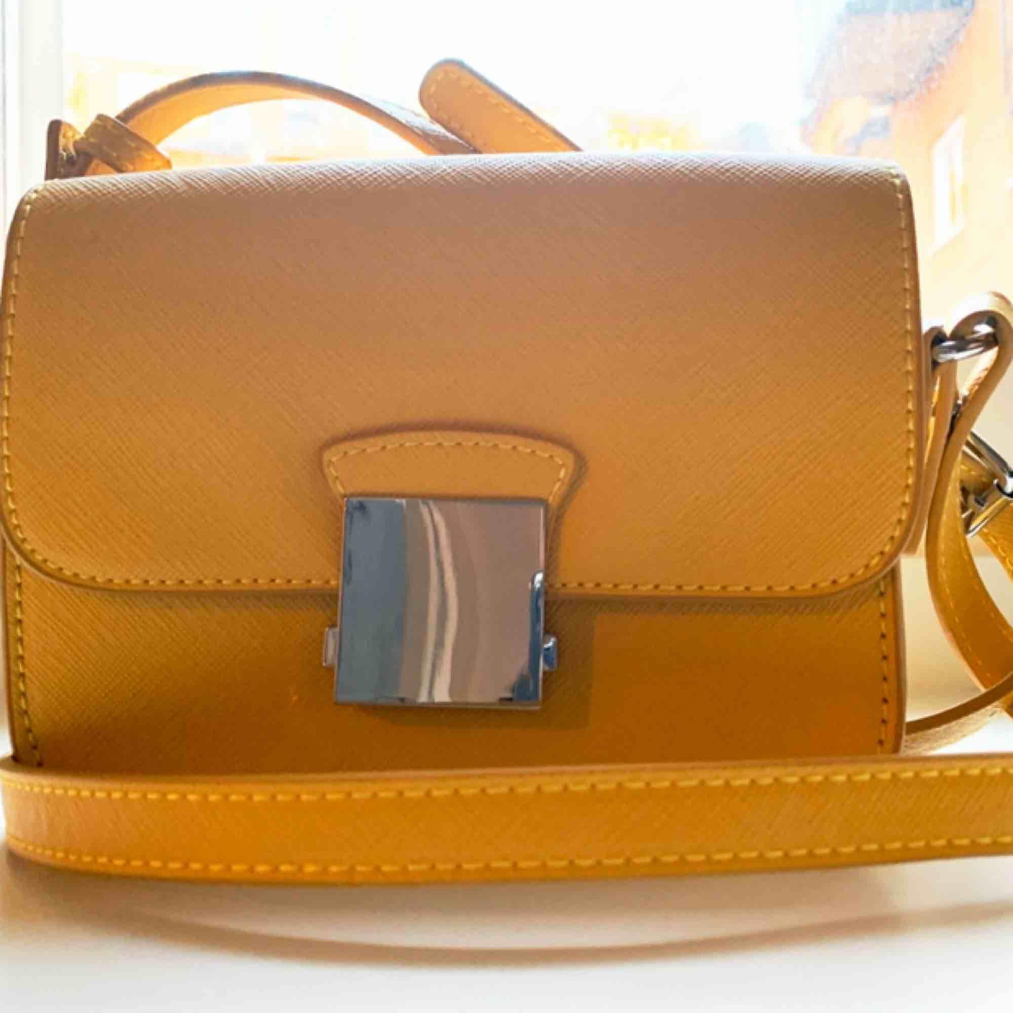 Axelremsväska i en klargul färg, rymmer mobil och det nödvändigaste. Avtagbar axelrem.. Väskor.