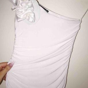 Lyxig one-shoulder klänning som passar perfekt till bröllop, dop, skolavslutning, student etc. Storlek: XS (extremt stretchigt så passar även S) Har endast används vid en kväll så skicket är mycket fint. Köpt för 599 kronor.