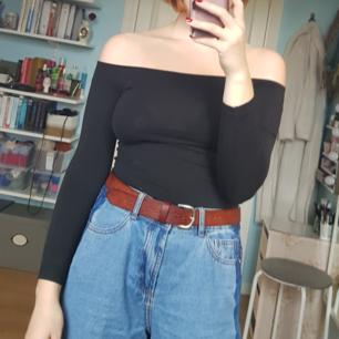 Enkel svart axellös tröja som kan matchas med nästan vad som helst, perfekt att ha i garderoben!