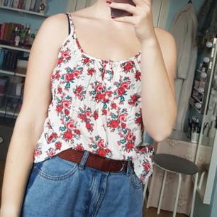 Otroligt gulligt linne med somrigt mönster av rosor, smala reglerbara axelband, lös passform och små knappar under urringningen