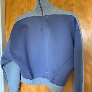 Helt oanvänd tjocktröja med hög hals och glansigt material på baksidan. Från Adidas by Stella McCartney.