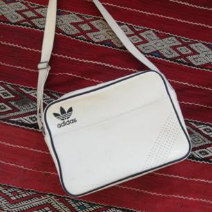 Vit vintage axelremsväska/messenger bag från Adidas, tror det är en tidigare version av Airliner-modellen. Ca 30x40 cm. Frakt 63 kr.