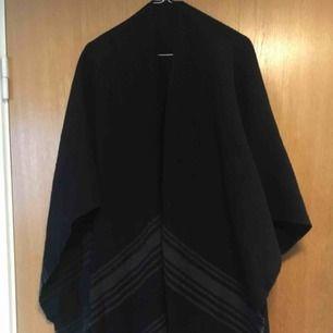 Sjal/poncho i stickat svart material med grå linjer och fransar. Funkar både som halsduk eller att hänga över en skinnjacka. Köpt i Kyoto, Japan för ca 300kr.