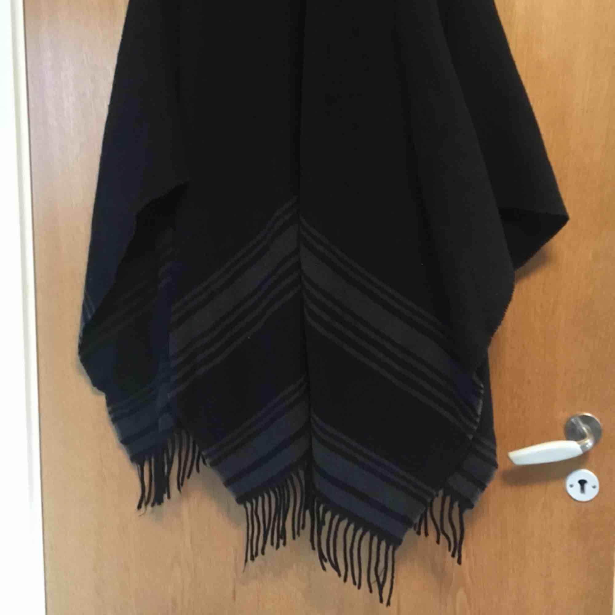 Sjal/poncho i stickat svart material med grå linjer och fransar. Funkar både som halsduk eller att hänga över en skinnjacka. Köpt i Kyoto, Japan för ca 300kr. . Accessoarer.