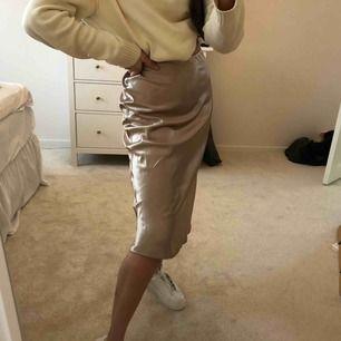 Trendig kjol i storlek S skulle jag säga, står inte i, men passar mig som har storlek S! Beige och glansig i silkes-liknande material. Oanvänd, men skulle behöva strykas :)