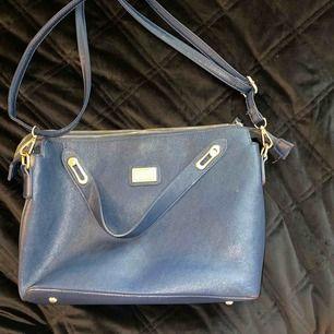 Mörkblå rymlig väska från Hampton Republic, med gulddetaljer. Köpt på Kappahl för några år sedan. Den är knappt använd men har legat ett tag i garderoben. Frakt tillkommer