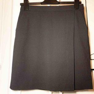 Kortare pennkjol med drapering. Snygg till business men också casual. Tyget är slätt. Längd mitt bak: 48cm