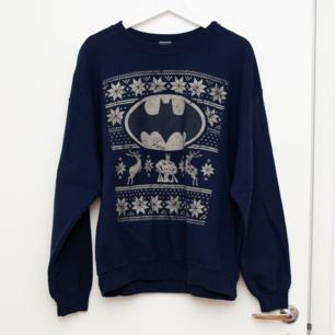 Mörkblå jultröja med Batmanmotiv i storlek L, normal i storleken. Sparsamt använd. Frakt tillkommer om köparen inte möts upp i Märsta. 🌸