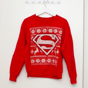 Röd jultröja med supermanmotiv i storlek S, normal i storleken. Sparsamt använd. Frakt tillkommer om köparen inte möts upp i Märsta. 🌸