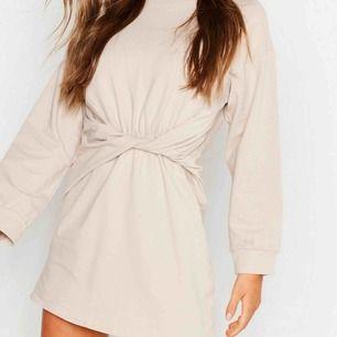 Fin beige sweatshirt klänning med en twist på magen. Köpt på bohoo för 299kr. Aldrig använd med prislappar på.  Storlek: 44 men sitter som en M  Betalas med swish och köparen står för frakt:)
