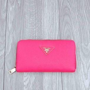 Rosa plånbok från Prada, vet ej om den är äkta. Bra skick förutom att dragkedjan inuti är svår att stänga.  Frakt kostar 42kr extra, postar med videobevis/bildbevis. Jag garanterar en snabb pålitlig affär!✨ ✖️Fraktar endast✖️